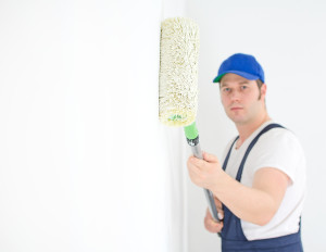 Painter In Uniform Paints The Wall. Focus On Roller Paint.